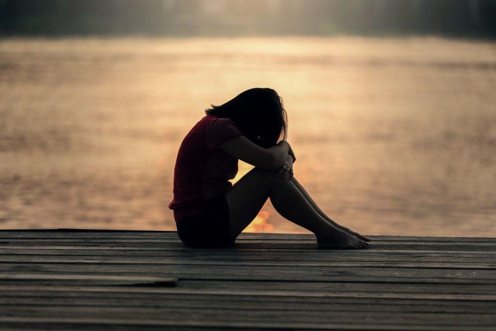 Smutná a sklamaná žena na moli pri mori plače