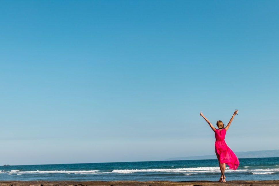 štastná žena na pláži v ružom šate