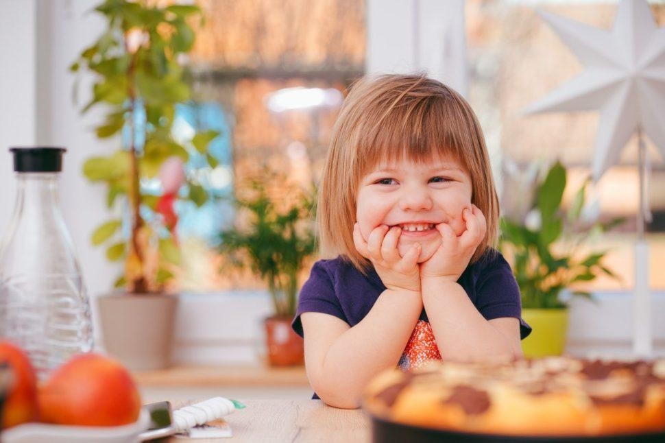 Malý prefikané dieťa pri stole na ranajkách